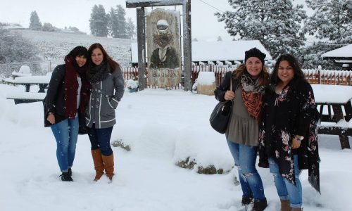group of women on a winter wine tour posing in front of The Hatch Winery sign in West Kelowna BC