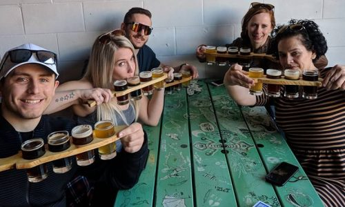 fun photo of group drinking beer tastings at Kettle River Brew Pub in Kelowna BC